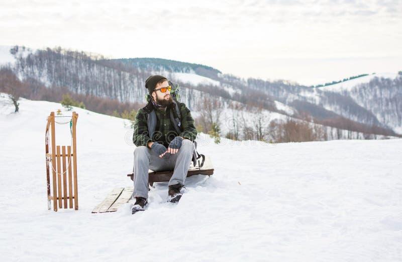 Hombre que se sienta en el top de la montaña con los trineos de madera fotos de archivo libres de regalías