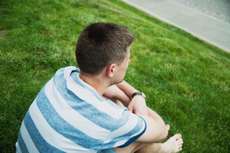 Hombre que se sienta en la hierba imágenes de archivo libres de regalías