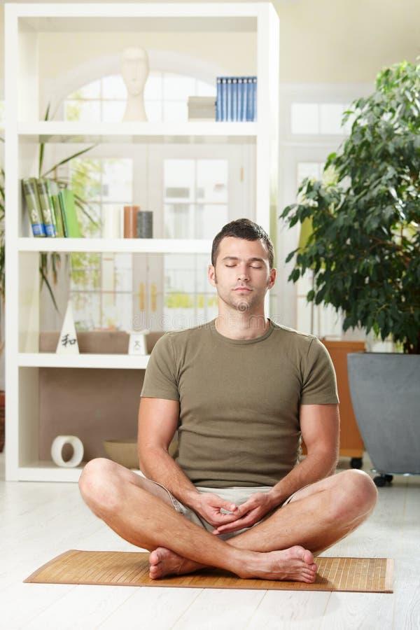 Hombre que se sienta en la posición de la yoga fotos de archivo