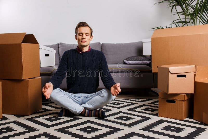 Hombre que se sienta en la posición de loto respecto a la alfombra contra el fondo de las cajas de cartón, sofá gris fotos de archivo