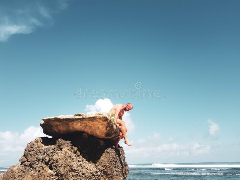 Hombre que se sienta en la roca fotografía de archivo
