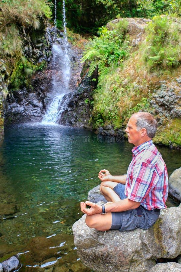 Hombre que se sienta en la roca que medita cerca de la cascada fotografía de archivo