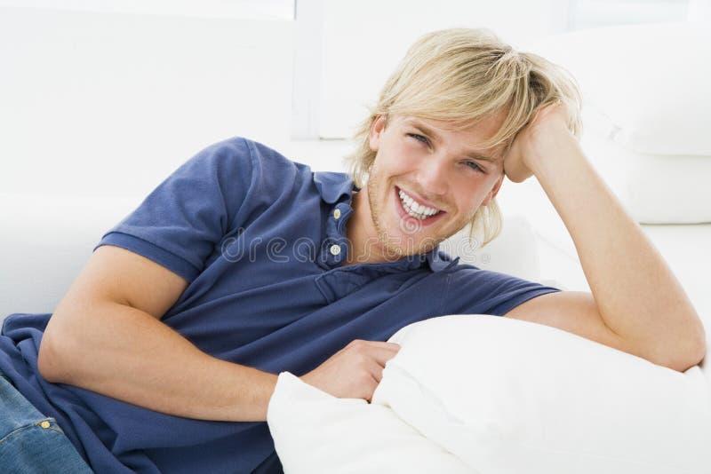 Hombre que se sienta en la sonrisa de la sala de estar imagen de archivo libre de regalías