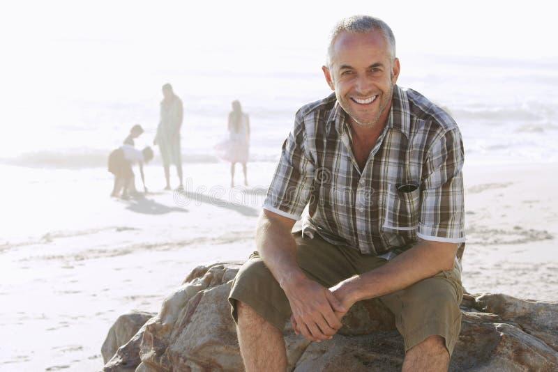 Hombre que se sienta en roca mientras que familia que goza en la playa fotos de archivo