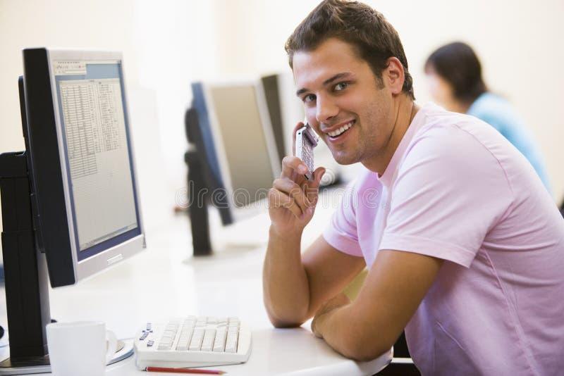 Hombre que se sienta en sala de ordenadores usando el teléfono imagen de archivo