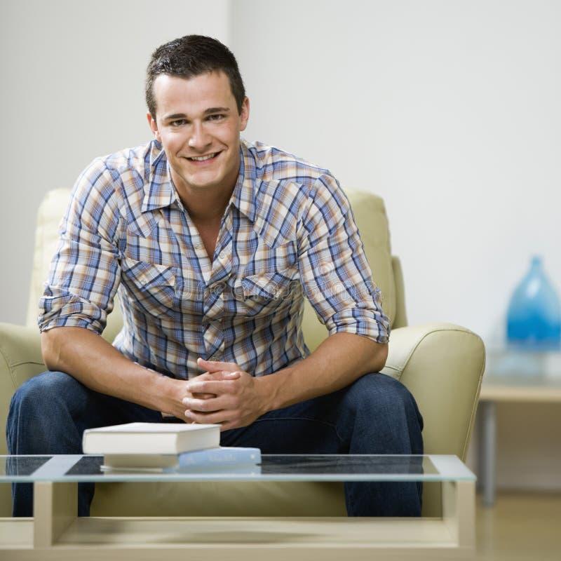 Hombre que se sienta en silla foto de archivo