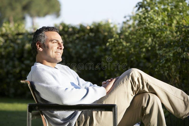 Hombre que se sienta en silla en patio trasero fotos de archivo libres de regalías