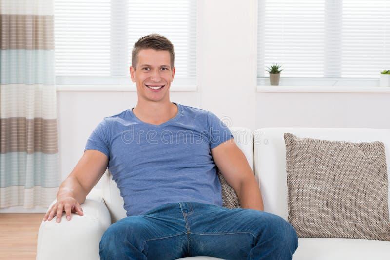 Hombre que se sienta en Sofa In Living Room imagenes de archivo
