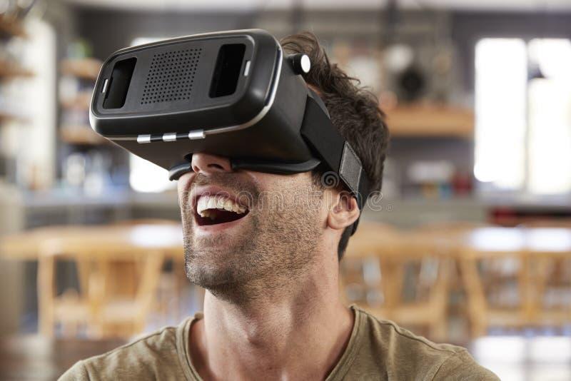 Hombre que se sienta en Sofa Wearing Virtual Reality Headset imagen de archivo