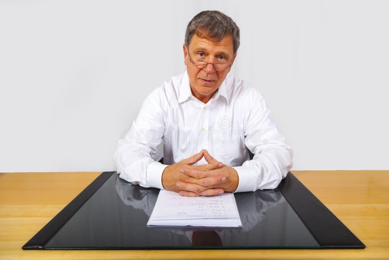 hombre que se sienta en su escritorio foto de archivo libre de regalías