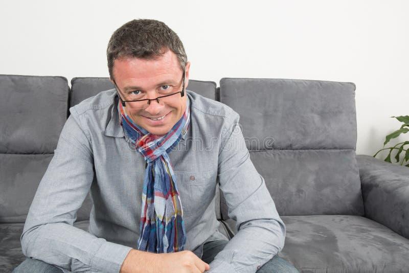Hombre que se sienta en su sofá en casa imagen de archivo