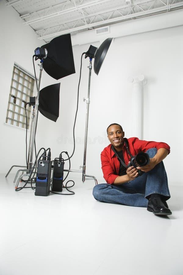 Hombre que se sienta en suelo con la cámara. fotografía de archivo