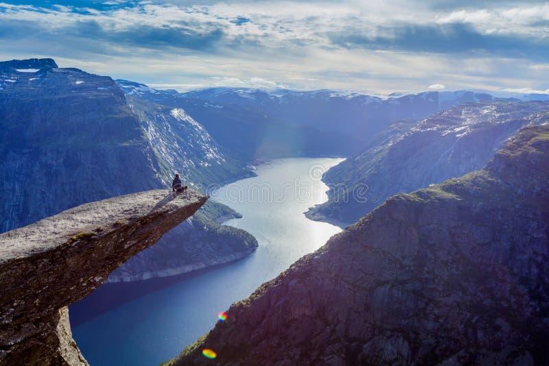 Hombre que se sienta en trolltunga en Noruega imagenes de archivo