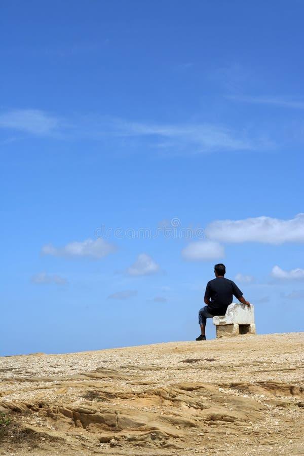 Hombre que se sienta en un banco imagen de archivo libre de regalías