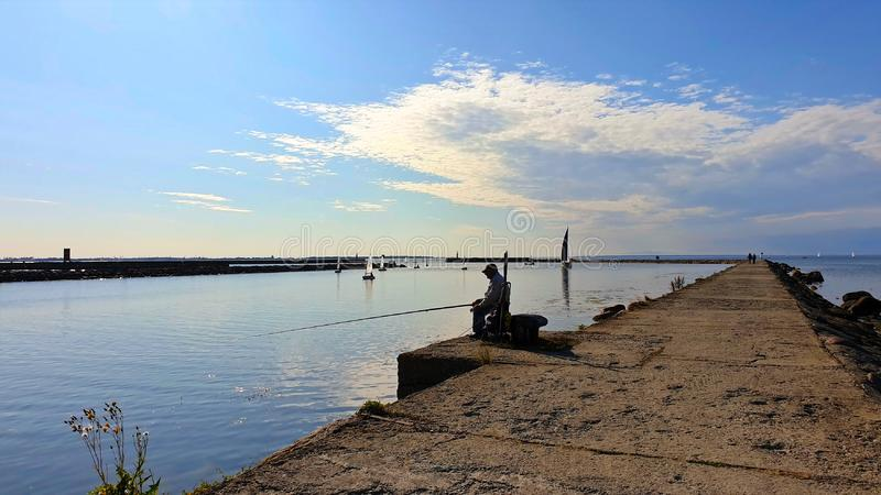 Hombre que se sienta en un embarcadero y que pesca en turismo de la bahía de Tallinn a la playa del paisaje marino del mar Báltic imagenes de archivo