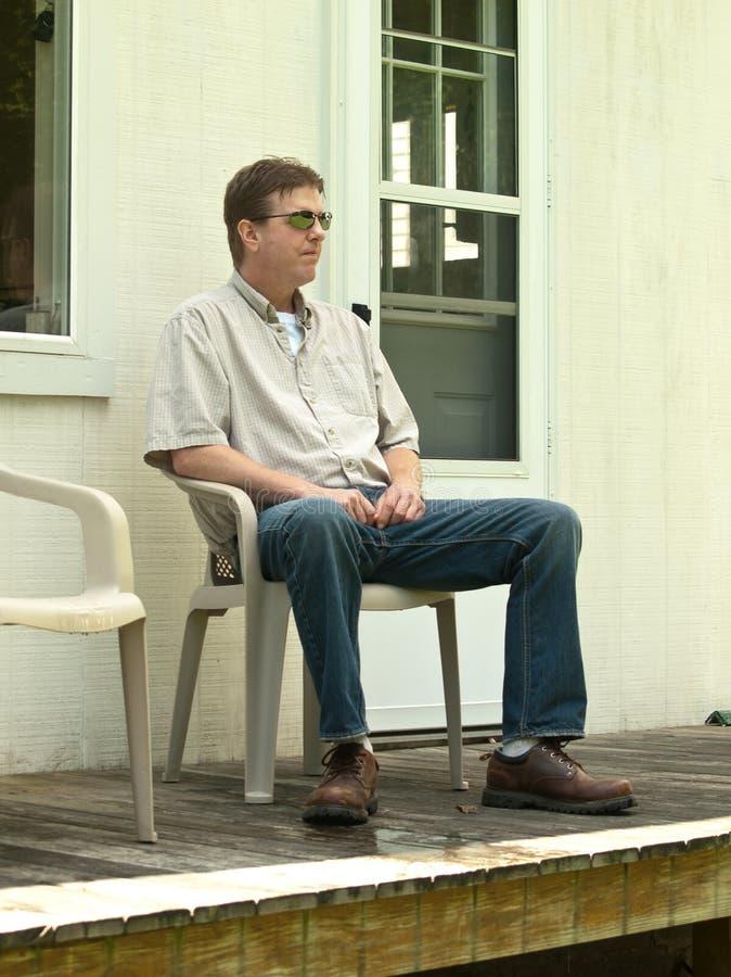 Hombre que se sienta en un pórtico imagenes de archivo