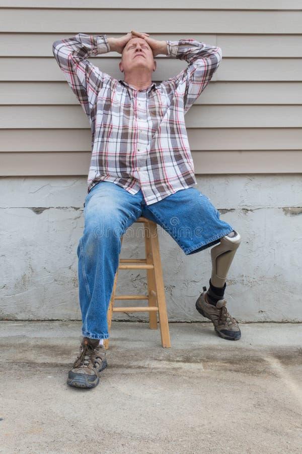 Hombre que se sienta en un taburete, pierna prostética del amputado hacia fuera, manos en la cabeza que mira para arriba fotos de archivo libres de regalías