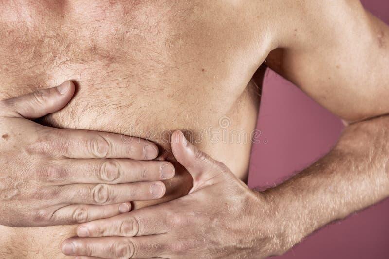 Hombre que se sostiene el pecho con ambas manos, teniendo el ataque del corazón o calambres dolorosos, presionando en pecho con l imagenes de archivo
