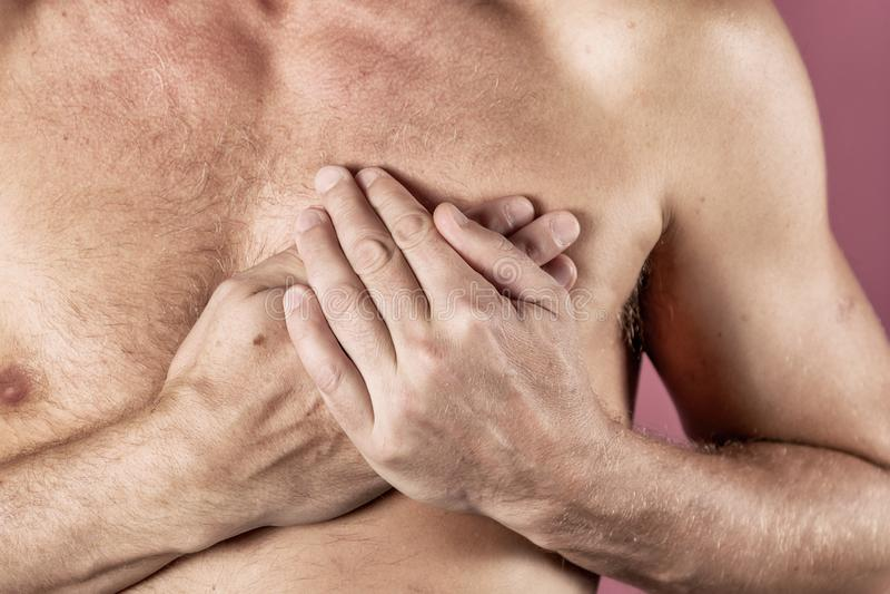 Hombre que se sostiene el pecho con ambas manos, teniendo el ataque del corazón o calambres dolorosos, presionando en pecho con l imagen de archivo