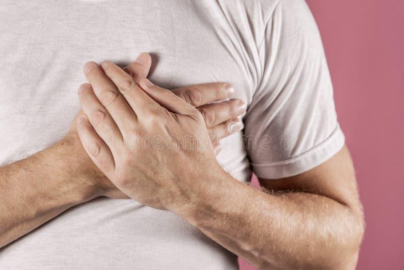 Hombre que se sostiene el pecho con ambas manos, teniendo el ataque del corazón o calambres dolorosos, presionando en pecho con l foto de archivo