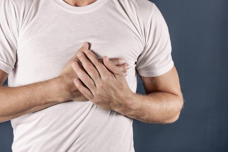 Hombre que se sostiene el pecho con ambas manos, teniendo el ataque del corazón o calambres dolorosos, presionando en pecho con l imagen de archivo libre de regalías
