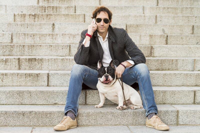 Hombre que sienta en las escaleras al lado de su perro y que habla por el teléfono fotografía de archivo libre de regalías