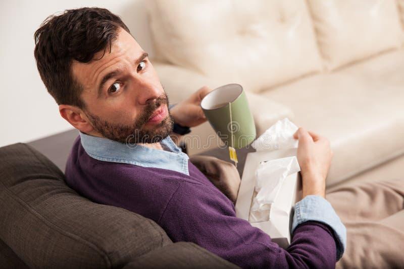 Hombre que siente enfermo en casa y té de consumición fotografía de archivo libre de regalías