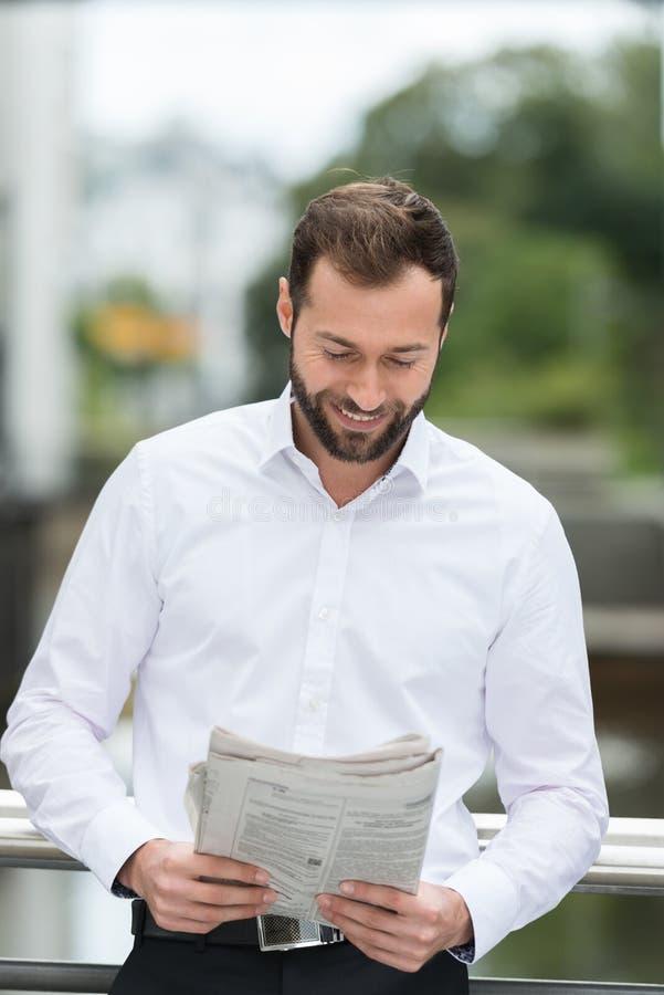 Hombre que sonríe como él lee el periódico al aire libre imagen de archivo libre de regalías