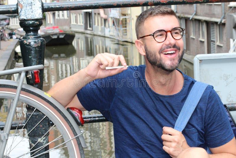 Hombre que sonríe en Amsterdam mientras que sostiene la junta foto de archivo