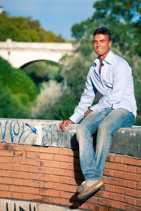 Hombre que sonríe en ciudad El esperar que se sienta en la pared baja fotografía de archivo