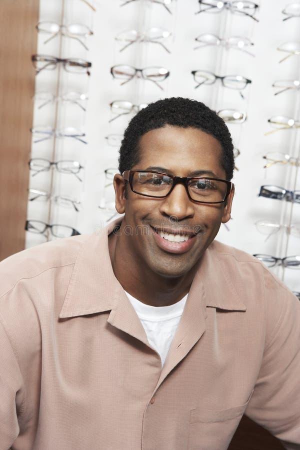 Hombre que sonríe en la tienda de las gafas fotografía de archivo