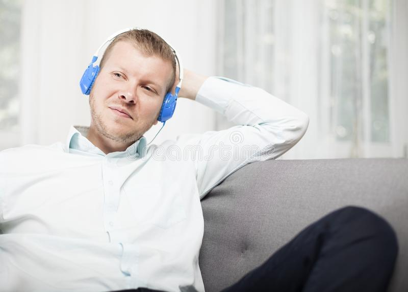 Hombre que sonríe a sí mismo como él escucha la música imagen de archivo