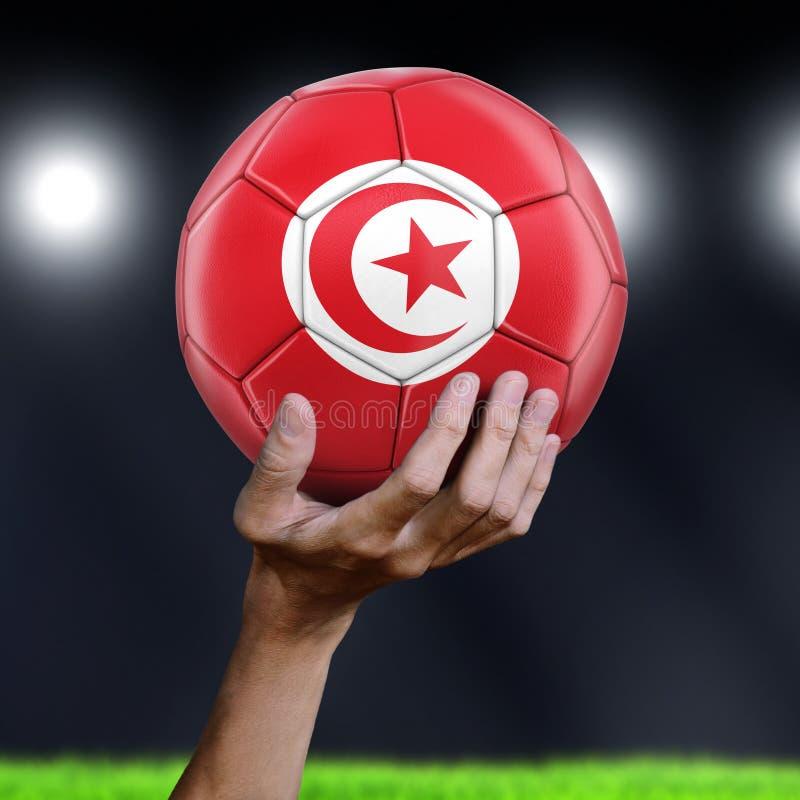 Hombre que sostiene el balón de fútbol con la bandera tunecina fotografía de archivo libre de regalías