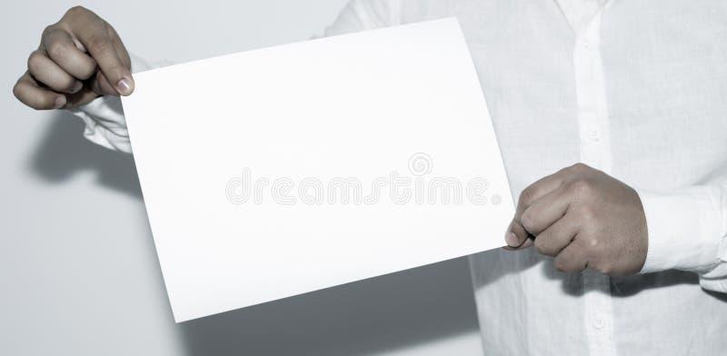 Hombre que sostiene el documento en blanco sobre el fondo blanco imagen de archivo libre de regalías
