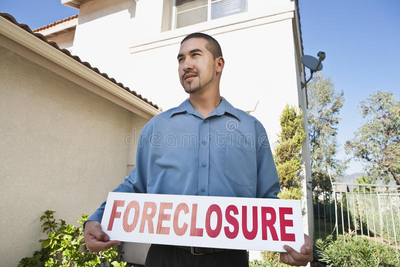 Hombre que sostiene el ~Foreclosure Sign~ imagen de archivo