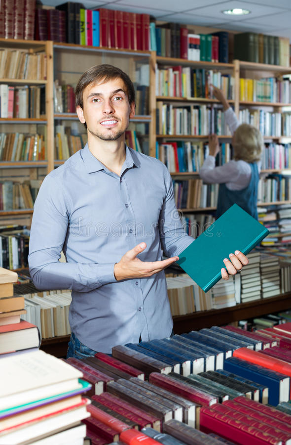 Hombre que sostiene el libro en difícilmente imagenes de archivo