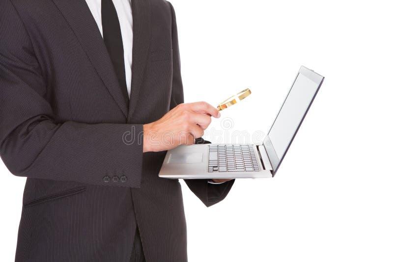 Hombre que sostiene el ordenador portátil y la lupa foto de archivo