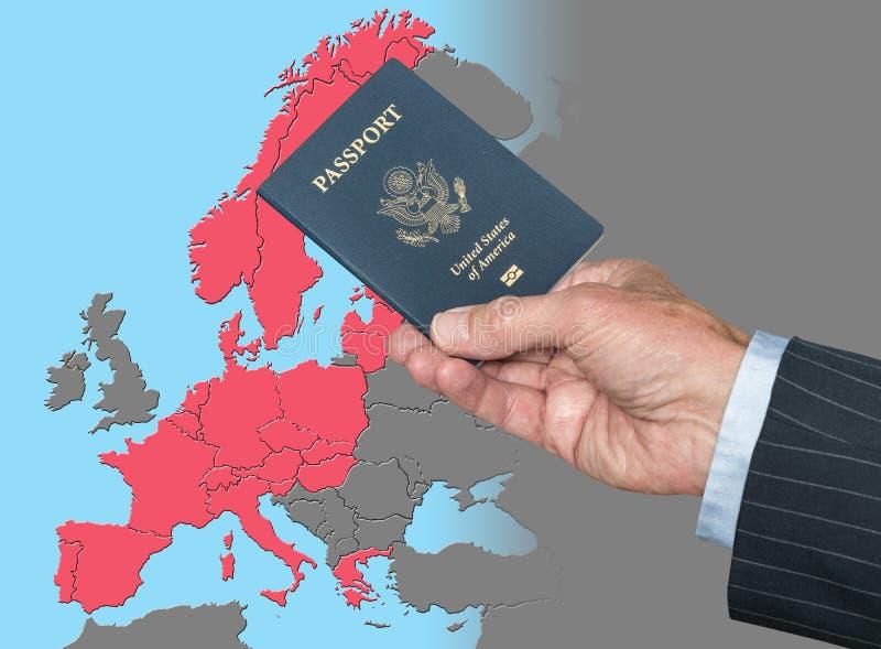 Hombre que sostiene el pasaporte de los E.E.U.U. en el mapa de la zona de Schengen fotografía de archivo