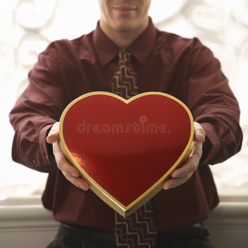 Hombre que sostiene el rectángulo en forma de corazón. foto de archivo