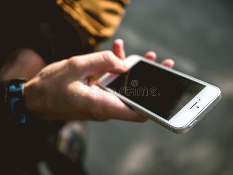 Hombre que sostiene el teléfono móvil en su mano fotos de archivo libres de regalías