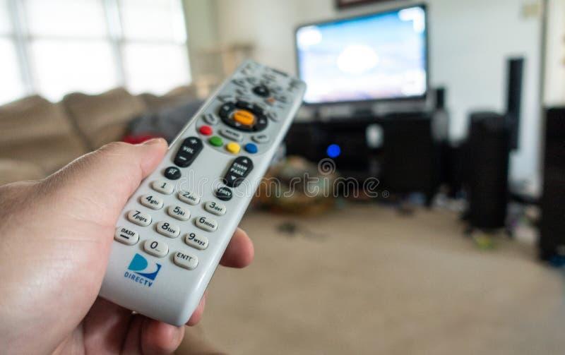 Hombre que sostiene el telecontrol de DirecTV imagen de archivo libre de regalías