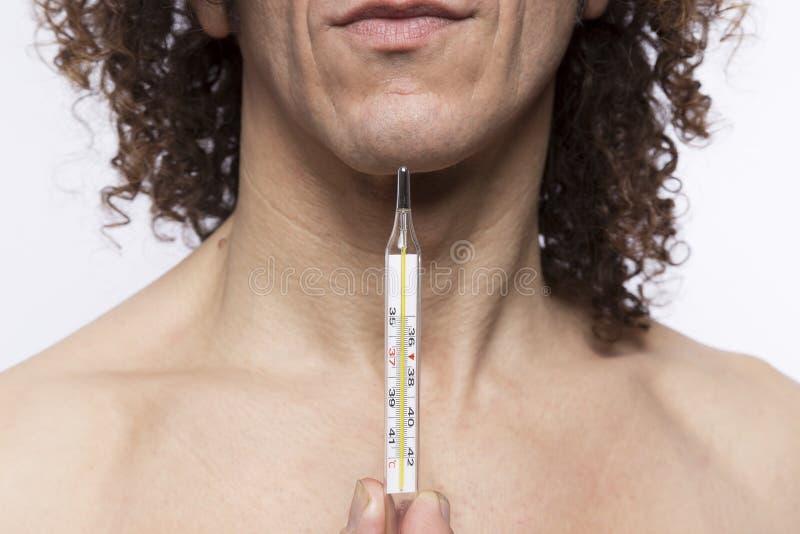 Hombre que sostiene el termómetro fotos de archivo