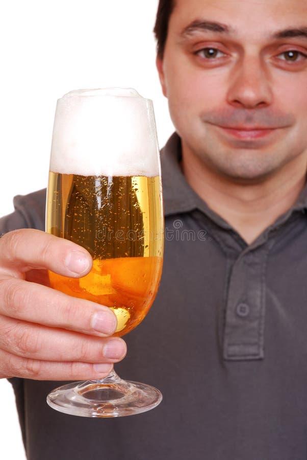 Hombre que sostiene el vidrio de cerveza lleno imagen de archivo