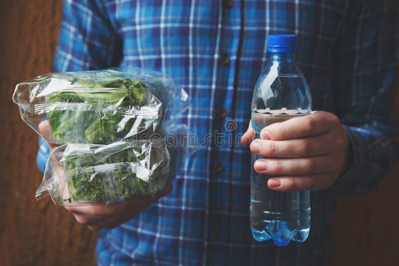 Hombre que sostiene la botella plástica azul no reutilizable de agua mineral y de ensalada verde fresca imagenes de archivo