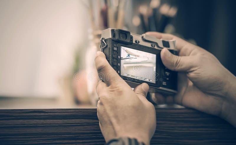 Hombre que sostiene la cámara del vintage que toma una foto foto de archivo
