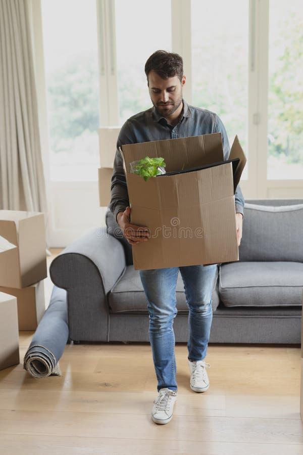 Hombre que sostiene la caja de cartón en nuevo hogar imágenes de archivo libres de regalías