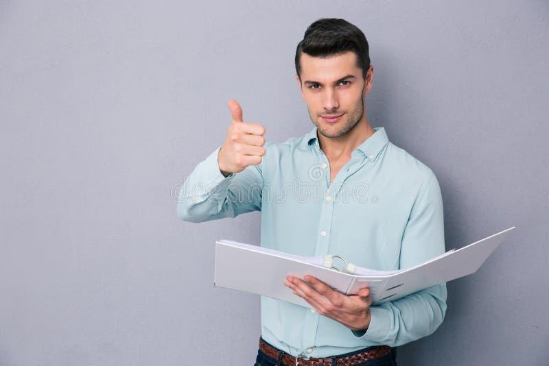 Hombre que sostiene la carpeta y que muestra el pulgar para arriba imagenes de archivo