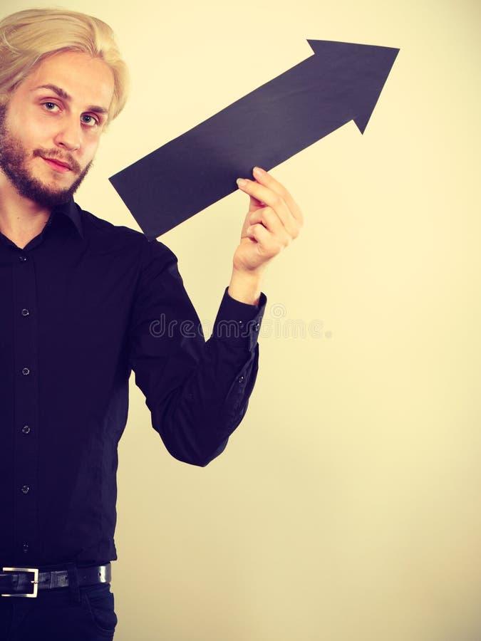 Hombre que sostiene la flecha negra que se?ala a la derecha imagen de archivo libre de regalías