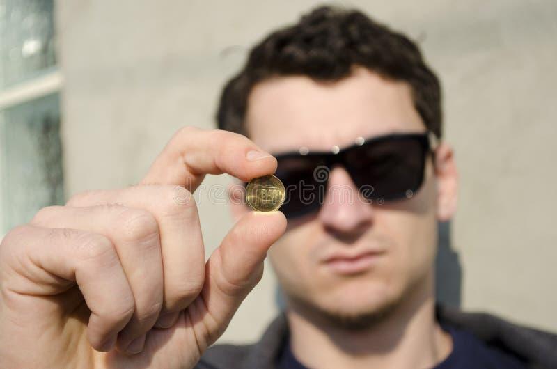 Hombre que sostiene la moneda imágenes de archivo libres de regalías
