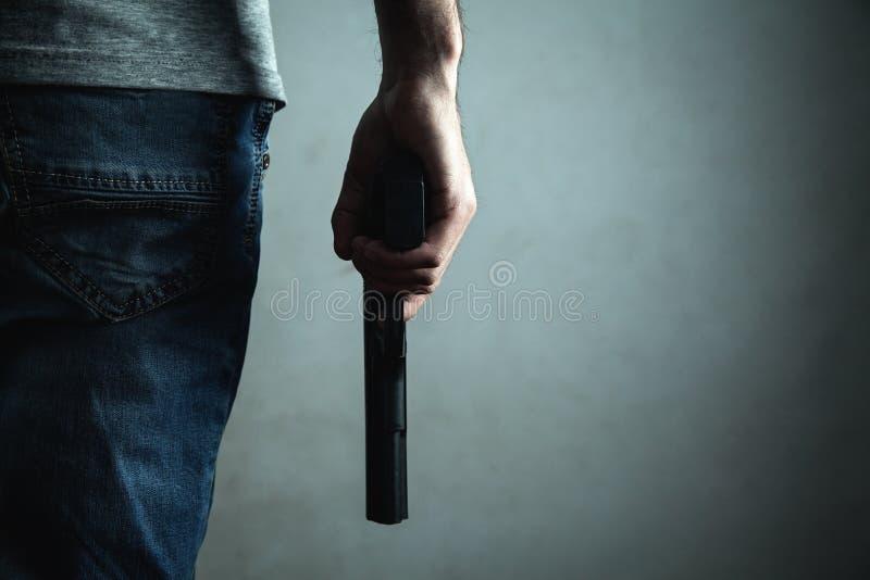 Hombre que sostiene la pistola Concepto criminal foto de archivo